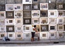 在坟墓前面的专栏的妇女打扫在一座公墓在安蒂波洛市,菲律宾 免版税库存图片