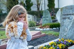 在坟墓前面的哀伤的女孩 免版税库存照片