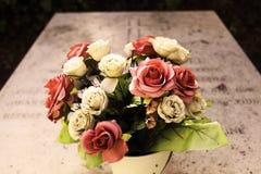 在坟茔坟墓的花在公墓 库存照片