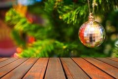 在垂悬在圣诞节tre分支的银色球的木桌  免版税图库摄影
