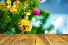 在垂悬在圣诞节tre分支的黄色球的木桌  免版税图库摄影