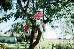 在垂悬在树的瓶子的花 免版税库存照片