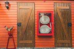 在垂悬在橙色木墙壁上的红色内阁的灭火水龙带 射击安全保卫系统的事故设备箱子 检查灭火器的人 免版税图库摄影