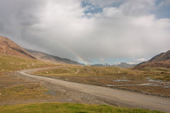 在垂悬在落矶山脉之间的农村路的云彩的彩虹 图库摄影