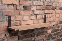 在垂悬在顶楼样式的一个砖墙上的木头和金属的架子 免版税库存图片