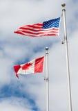 在垂悬在Th的一个旗杆的杆的美国和加拿大旗子 免版税库存图片