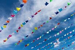 在垂悬外面为假日wi的绳索的小逗人喜爱的五颜六色的旗子 库存照片