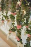 在垂悬的背景的花与在婚礼聚会的白色墙壁在葡萄酒样式 免版税图库摄影