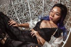 在垂悬的藤条椅子的可爱的亚裔妇女 库存图片