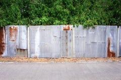 在垂直的样式纹理的老多彩多姿的生锈的锌篱芭与高龙眼绿色树和混凝土路背景 图库摄影