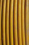 在垂直的卷的黄色铜电缆 库存照片