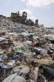 在垃圾堆积场的一个挖掘机装载者 免版税库存照片