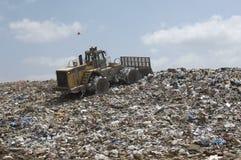 在垃圾堆积场的挖掘机装载者 免版税库存照片