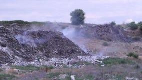 在垃圾填埋的抽烟的垃圾 搜寻在家庭废物中的两可怜的人有用的事 影视素材