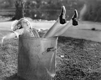在垃圾桶下落的妇女在路旁(所有人被描述不更长生存,并且庄园不存在 供应商warran 免版税库存照片