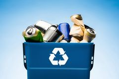 在垃圾桶的各种各样的金属罐头与回收标志 免版税库存照片