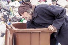 在垃圾箱的无家可归者搜查垃圾填埋 库存照片
