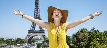 在埃佛尔铁塔前面的微笑的少妇欣喜在巴黎 免版税图库摄影