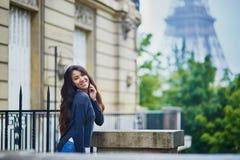 在埃佛尔铁塔前面的愉快的少妇 库存照片