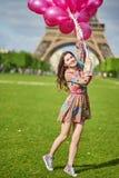在埃佛尔铁塔附近的女孩在有巨大的束的巴黎桃红色气球 库存照片