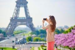 在埃佛尔铁塔附近的美丽的妇女在采取与她的手机的巴黎selfie 免版税库存图片