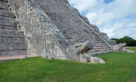 在埃尔卡斯蒂约金字塔的台阶的基地的用羽毛装饰的蛇在奇琴伊察考古学站点,墨西哥的 免版税库存照片