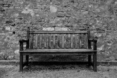 在城堡墙壁前面的一条被风化的长凳 免版税库存图片