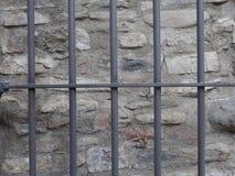 在城堡墙壁前面的金属门 库存照片