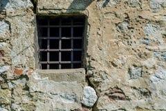 在城堡细胞壁的老监狱窗口有金属棒的 库存照片