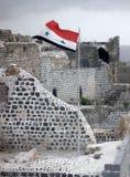 在城堡Marqab的墙壁上的叙利亚旗子在风振翼 库存图片
