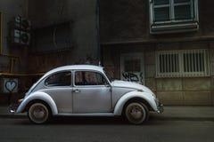 在城市中间停放的白色大众甲壳虫 免版税图库摄影