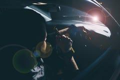 在城市供以人员饮料啤酒,当危险地驾驶在晚上,左手驱动系统时 免版税图库摄影