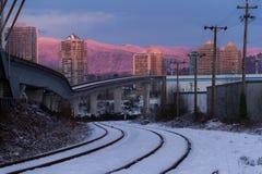 在城市倒空路轨,当五颜六色的日落在冬天时 库存照片
