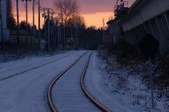在城市倒空路轨,当五颜六色的日落在冬天时 库存图片