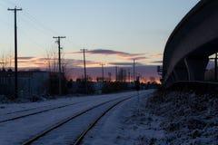 在城市倒空路轨,当五颜六色的日落在冬天时 免版税库存图片