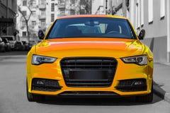 在城市停放的黄色豪华汽车 免版税库存照片