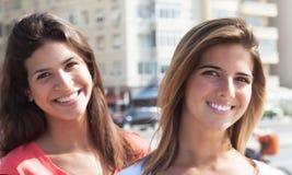 在城市嘲笑照相机的两个女朋友 免版税库存照片