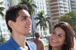 在城市嘲笑照相机的两个女朋友 免版税库存图片