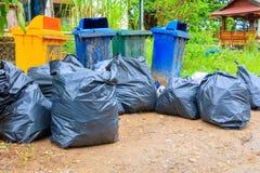 在城市堆黑垃圾袋塑料和四个垃圾箱肮脏的路旁 库存照片