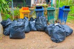 在城市堆黑垃圾袋塑料和四个垃圾箱肮脏的路旁 库存图片
