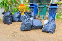 在城市堆黑垃圾袋塑料和四个垃圾箱肮脏的路旁 免版税库存照片