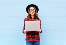 在城市塑造拿着便携式计算机的年轻微笑的妇女,穿在蓝色背景的黑帽会议红色方格的衬衣 免版税库存图片