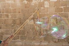 在城市墙壁的背景的巨大的肥皂泡 免版税库存图片