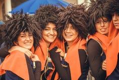 在城市天期间,传统黑帽会议的年轻愉快的英王乔治一世至三世时期女孩在人人群  免版税图库摄影