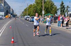 在城市天本机活动期间,射击他在录影奔跑最后阶段生活竞争的运动员竞争者和人 免版税图库摄影