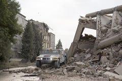 在城市废墟中间的军事发嗡嗡声的东西,倒塌的房子 库存照片