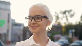 在城市微笑在日落背后照明的年轻美丽的白肤金发的妇女画象  免版税图库摄影