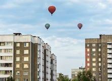 在城市房子屋顶的三个气球  免版税图库摄影