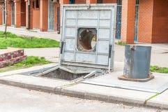 在城市打开一个地下垃圾容器的盖子在街道上的 免版税图库摄影