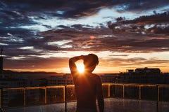 在城市现出轮廓站立在游泳池的一个人在日落在夏天 免版税库存照片